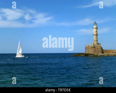 White Yacht Sailing near the Historic Lighthouse at Old Venetian Harbor in Chania, Crete Island of Greece - Stock Photo