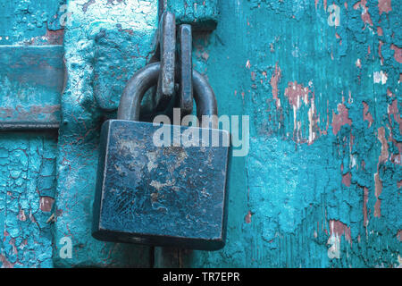 Vintage padlock closed hasps on scratched painted door. Concept of security and privacy protection. Textured grunge background - Stock Photo