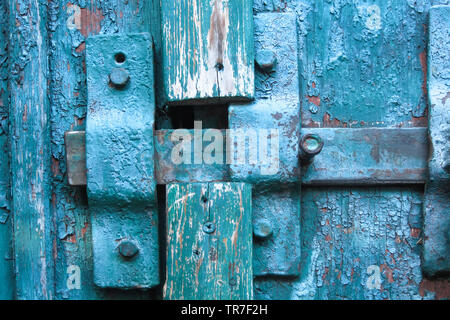 Vintage closed latch on weathered scratched wooden door. Concept of security and privacy protection. Textured grunge background - Stock Photo