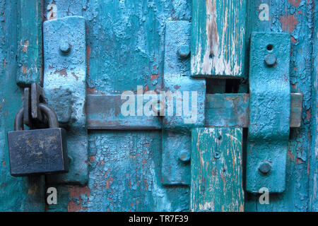 Vintage latch and closed padlock on weathered scratched wooden door. Concept of security and privacy protection. Textured grunge background - Stock Photo