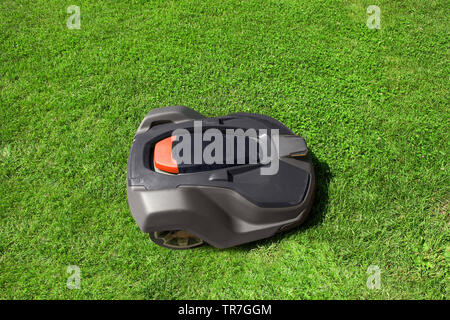 Automatic robot lawnmower mows grass on green lawn. Automated lawn mower cutting plants in summer garden near house. Modern gardening equipment, top - Stock Photo
