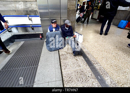 London, England, UK. Two homeless men by the entrance to Victoria Station - Stock Photo