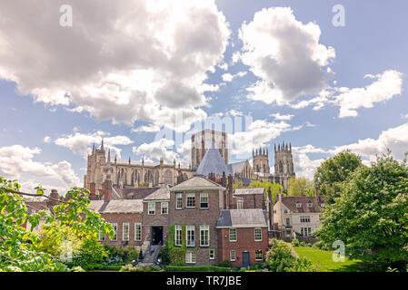 York Minster rises from amongst some elaborate  buildings arrayed in front of it.  Dramatic clouds are above. - Stock Photo