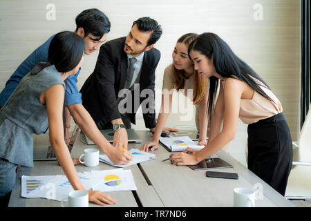 Smart manager explaining internal meeting to his project team in modern office. The multi ethnic business person group in suit. Project and Business c - Stock Photo
