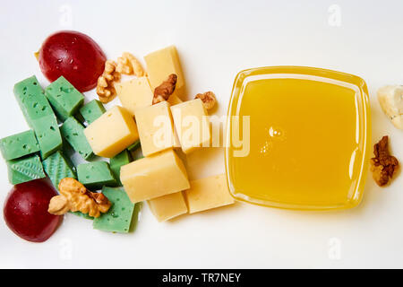 Slicing cheese with nuts, grapes and honey on a white plate. - Stock Photo