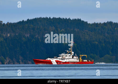 A side view of a Coast Guard vessel traveling through the Strait of Georgia near Vancouver Island British Columbia - Stock Photo