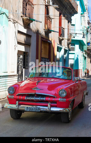 Classic American 1950's red car driving through a dilapidated street in the Old Town (Habana Vieja) of Havana, Cuba, Caribbean - Stock Photo