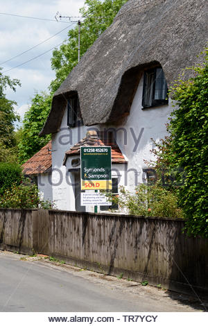 Picturesque view of a rural thathed cottage with a Symonds & Sampson Sold board outside, Dorset, England, UK - Stock Photo