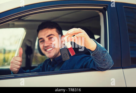 Young casual man wearing blue shirt holding car keys out of the window, showing thumb up positive gesture and smiling. New driver on the road concept. - Stock Photo