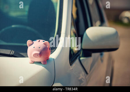 New car with pink piggy money bank on the hood, outdoors sunny background. Dealership offering credit finance services. Auto leasing, vehicle purchase - Stock Photo