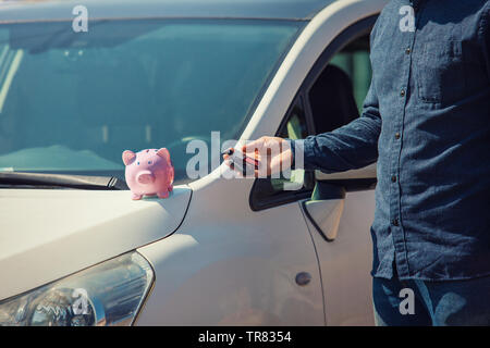 Man outdoors holding his new car keys and pink piggy money bank on the hood. Dealership offering credit finance services. Auto leasing, vehicle purcha - Stock Photo