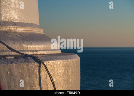 Foundation of a lighthouse at sunset. - Stock Photo