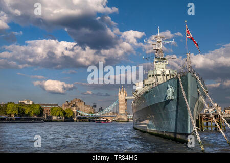 HMS Belfast ship flying Union Jack Flag, moored on River Thames in late afternoon sunlight, with Tower Bridge and The Tower Hotel behind London SE1 - Stock Photo