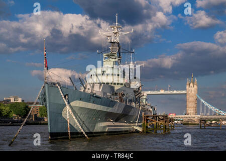 HMS Belfast tourist attraction ship, moored on River Thames in late afternoon sunlight, with Tower Bridge and London Red Bus crossing London SE1 - Stock Photo