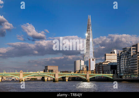 The London Shard with sunburst and light reflection in River Thames, South Bank with Southwark Bridge and London Bridge behind Southwark London UK - Stock Photo