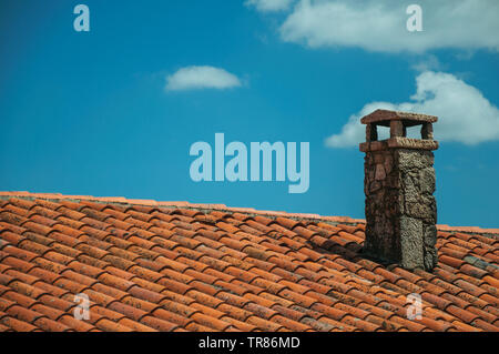 Rooftop covered by clay shingles from an old house and stone chimneys at Sortelha. An astonishing and well preserved medieval hamlet in Portugal. - Stock Photo