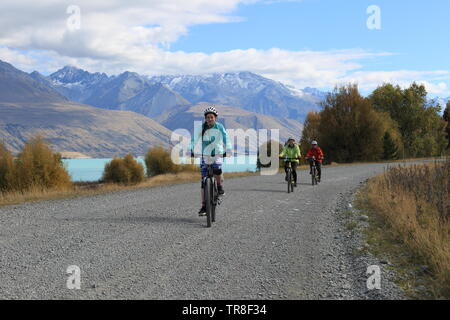 Cyclists by Lake Pukaki on Alps 2 Ocean cycle trail, New Zealand - Stock Photo