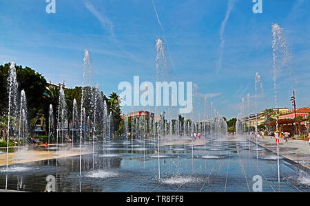 Promenade du Paillon in Nice, France, and its fountains on a summer day. People are walking and enjoying a beautiful pack and fountains. - Stock Photo