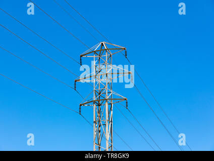 transmission tower against a brilliant blue sky - Stock Photo