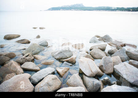 Stones on Shore in La Colba Bay on North Sardinia, Italy. Beach of Rena di Ponente. Sardinia is the Second Largest Island in Mediterranean Sea. - Stock Photo