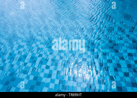 Swimming Pool with Sun Reflection. Surface of Blue and White Pool Water Background of Summer Vacation. Top view of Aqua Ripple on Blue Tiled Texture. - Stock Photo