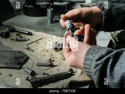 Mechanics repairing a diesel injector.  Workers hands is holding  micrometer. A man measures the thickness of spare parts to the injector. - Stock Photo