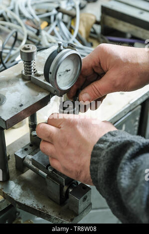 Mechanics a repairing a diesel injector. Worker's hands holds the injector. A man measures the depreciation of the nozzle. - Stock Photo