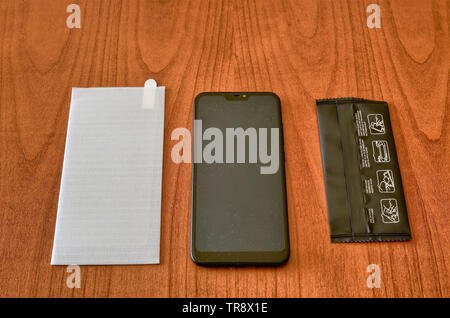 Preparation of the material to install a protective glass cover on the smartphone screen. The sachet with the screen cleaning kit was opened on the wo - Stock Photo