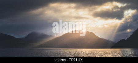 Morning light and mood by the Romsdalsfjorden, Norway. Sun rays breaking through the clouds, early morning warm light. - Stock Photo