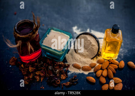 Close up of herbal face pack for removing black and white heads on wooden surface i.e. Multani mitti or fuller's earth with rose water and almond oil. - Stock Photo