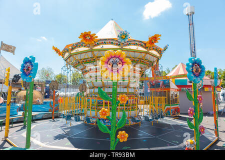 Bergamo, Italy - May 2019: carousel chains for children in bright colors during a fair in an Italian park flower shaped lights. Spring, beautiful day - Stock Photo