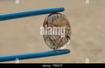 Rutilated Quartz black needles and copperi red hematite inclusion - Stock Photo