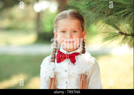 Smiling child girl 6-7 year old posing outdoors. Wearing white shirt with red bow tie. Back to school. Childhood. - Stock Photo