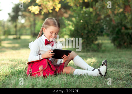 Smiling kid girl 6-7 year old sitting and playing tablet outdoors. Wearing school uniform. - Stock Photo