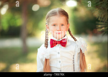 Kid girl 6-7 year old smiling outdoors. Wearing white shirt and red bow tie. Looking at camera. - Stock Photo