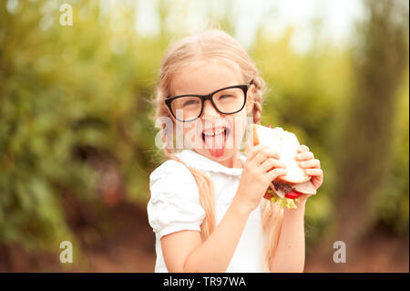 Funny kid girl eating sandwich outdoors. Having fun. Looking at camera. Posing over nature background. Healthy food. Childhood. - Stock Photo