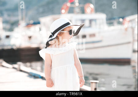 Cute baby girl 3-4 year old wearing dress, hat and sun glasses over sea background. Summer season. - Stock Photo