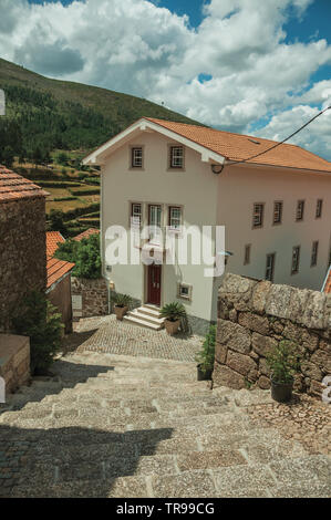 Two-story house at the end of deserted alley on slope with steps at Alvoco da Serra. A cute village clinging on a steep valley in eastern Portugal. - Stock Photo