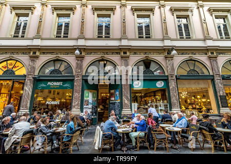 People sitting down drinking coffee outside Mokafe cafe in  Les Galeries Royales Saint-Hubert , an elegant glazed shopping arcade in Brussels ,Belgium - Stock Photo