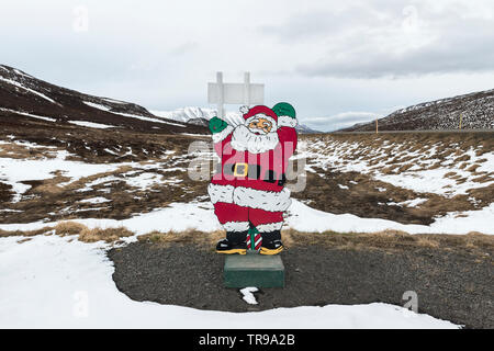 A Father Christmas figure beside the ring road in the mountains of north Iceland - Stock Photo