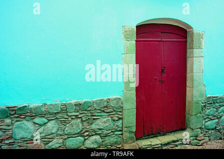Red wooden door on the concrete and stone wall in aqua blue color - Stock Photo