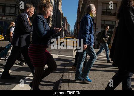 SMS-Nachrichten beim Überqueren der Straße könnten in NYC bald illegal werden. // Texting while crossing the street might soon become illegal in NYC / - Stock Photo