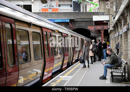 Passengers commuters boarding an underground train carriage at Barbican Station in the City of London UK England  KATHY DEWITT - Stock Photo