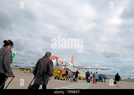 Passengers with carry on luggage at Lisbon airport walking across the tarmac to board an Easyjet plane to fly to London England UK  2019 KATHY DEWITT - Stock Photo