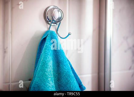 Blue towel hanging on hanger in bathroom.  Shallow depth of field. Closeup. - Stock Photo