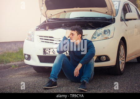 Desperate young man driver seated on the asphalt ground in front of his car open hood. Vehicle breakdown concept. Guy motorist has problems with autom - Stock Photo