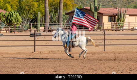 Weekly rodeo at White Stallion Ranch, a dude ranch outside Tucson, AZ. Carrying the American Flag, always the start of the rodeo. - Stock Photo