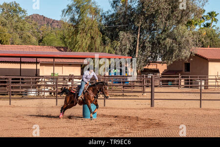 Weekly rodeo at White Stallion Ranch, a dude ranch outside Tucson, AZ. Barell racing, a timed event limited to woman riders. A topnotch barrel race ho - Stock Photo