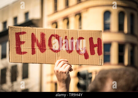 Protester holds up cardboard sign saying 'ENOUGH' at the March for our Lives rally in Washington, DC, USA on March 24, 2018. - Stock Photo