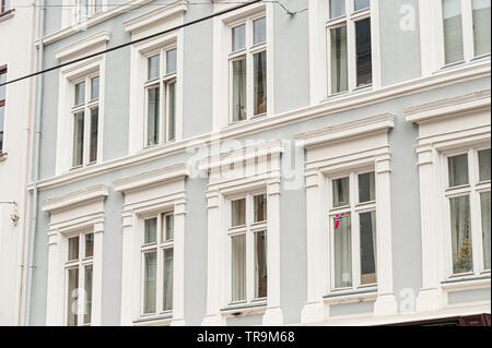 Facade with windows on a blue building. A single, small norwegian flag in one of the windows. - Stock Photo